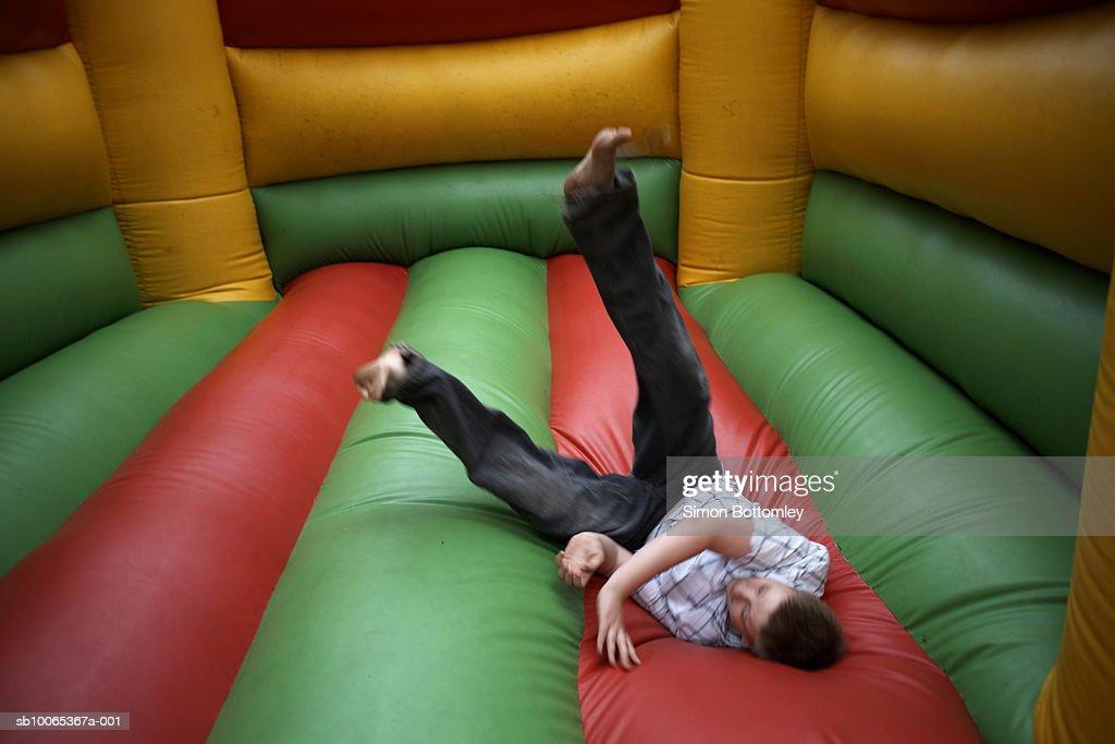 Teenage boy (13-14) jumping in bouncy castle : Foto stock
