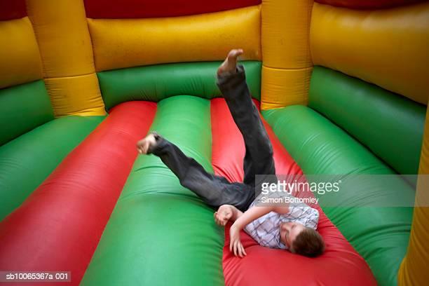 Teenage boy (13-14) jumping in bouncy castle