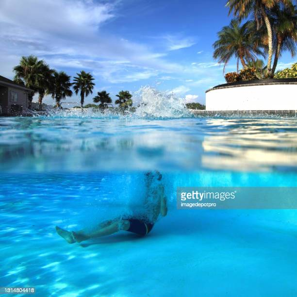 teenage boy jumping in to swimming pool - partially sighted stock pictures, royalty-free photos & images