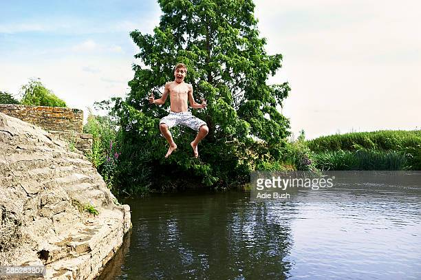 Teenage boy jumping mid air into lake