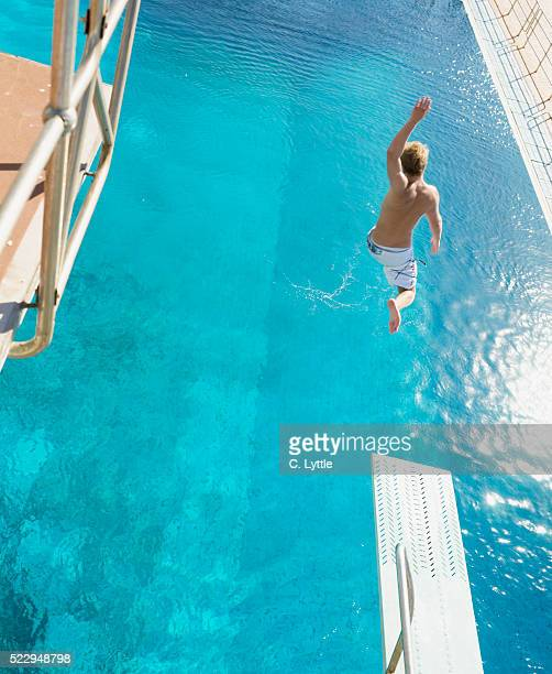 Teenage Boy Jumping off Diving Board