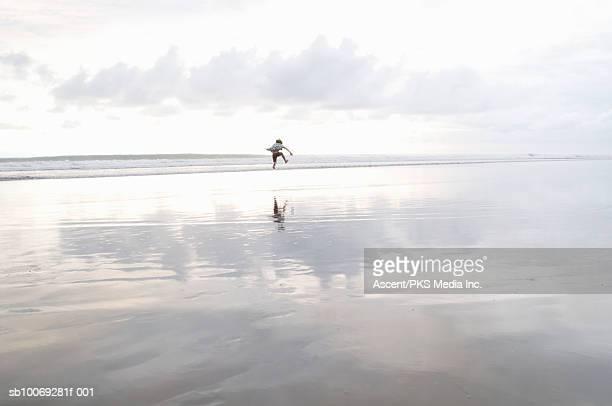 Teenage boy (14-15) jumping on beach