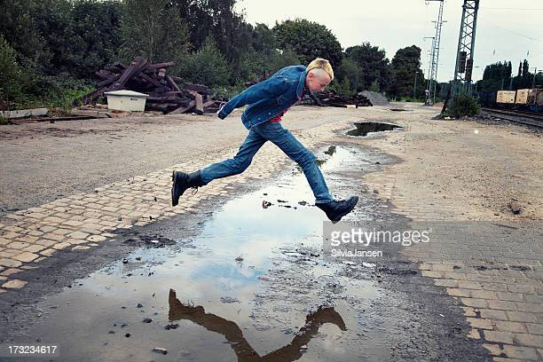 teenage boy jumping over a puddle
