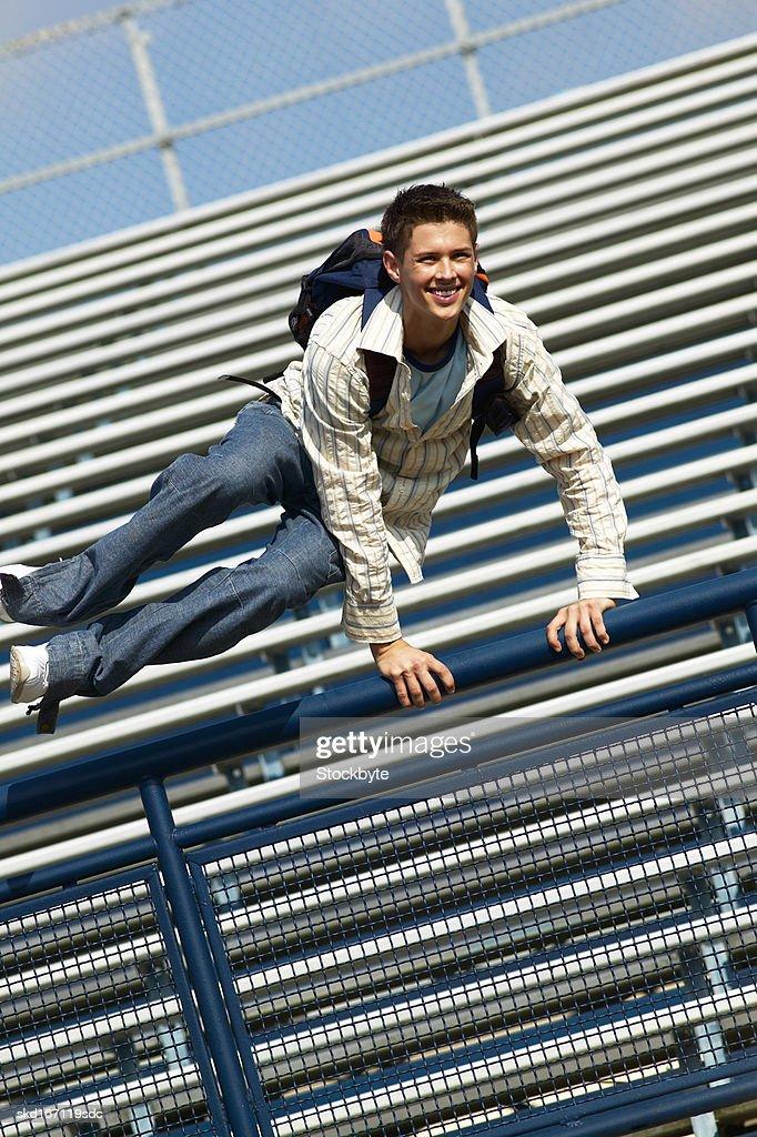 teenage boy (16 - 18) jumping over a railing : Stock Photo