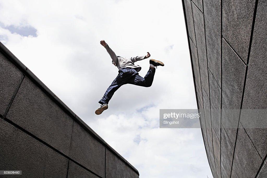 Teenage boy (16-16) jumping over gap between walls : Stock Photo