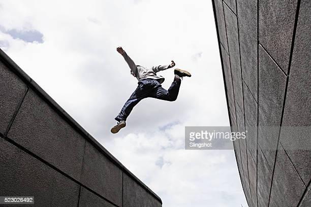 teenage boy (16-16) jumping over gap between walls - le parkour stock-fotos und bilder