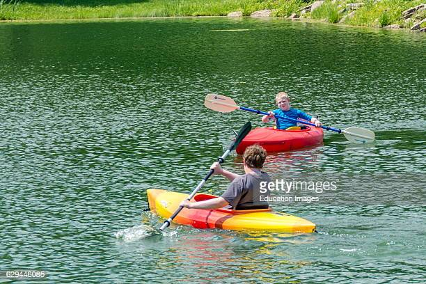 Teenage boy kayaking on a lake.