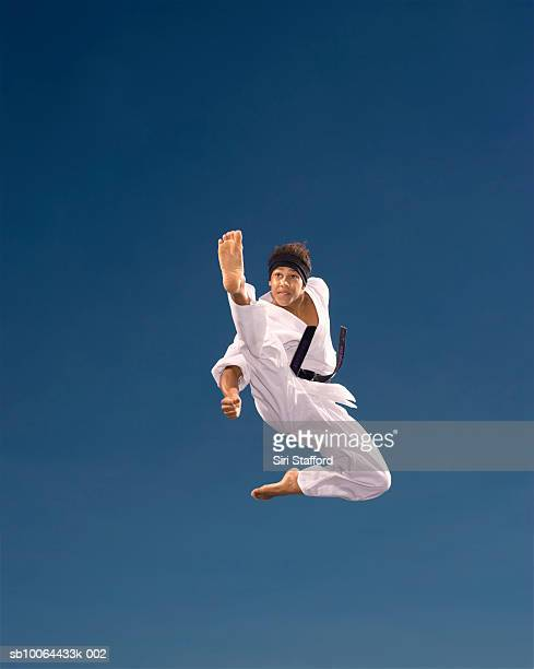 Teenage boy (14-15) kicking in mid-air, low angle view