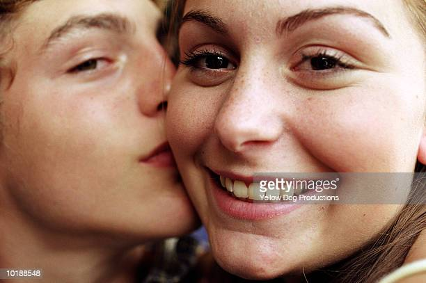 Teenage boy(14-16) kissing girl on cheek