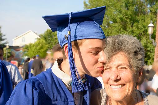 Teenage boy kissing grandmother at graduation ceremony - gettyimageskorea