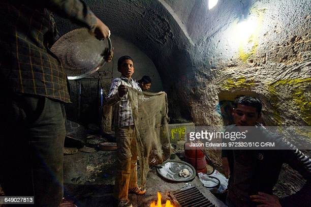 Teenage boy labourers heating and polishing copper and silver platters and pots in a workshop in a bazaar.