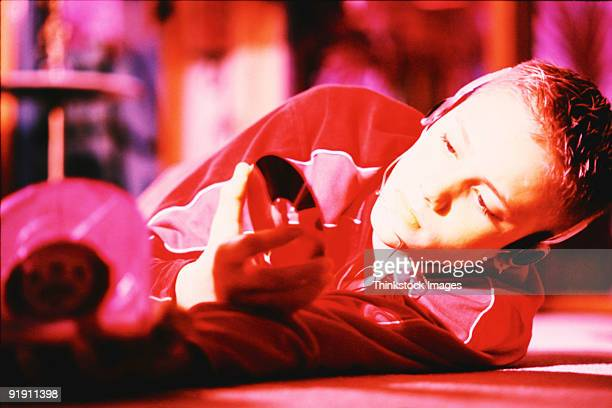 teenage boy laying on floor, wearing headset, holding cd - personal compact disc player stock pictures, royalty-free photos & images
