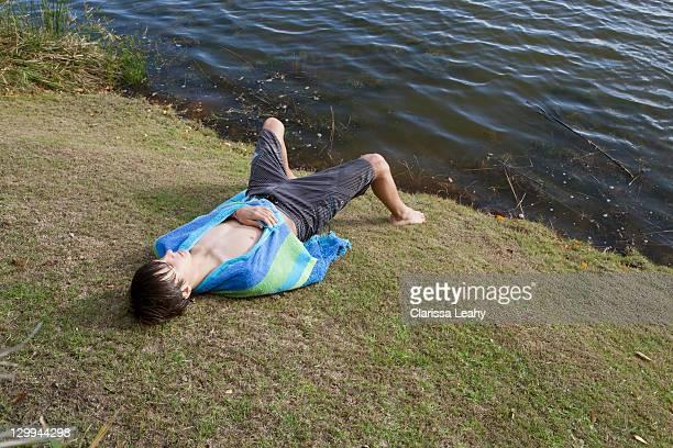 Teenage boy laying on riverbank