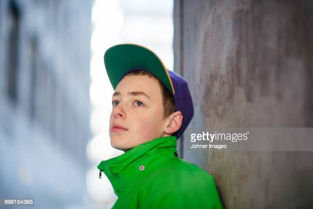 Teenage boy leaning against wall in city