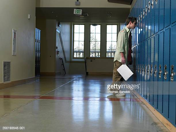 teenage boy (12-14) leaning head against lockers in hallway, side view - armário com fechadura - fotografias e filmes do acervo