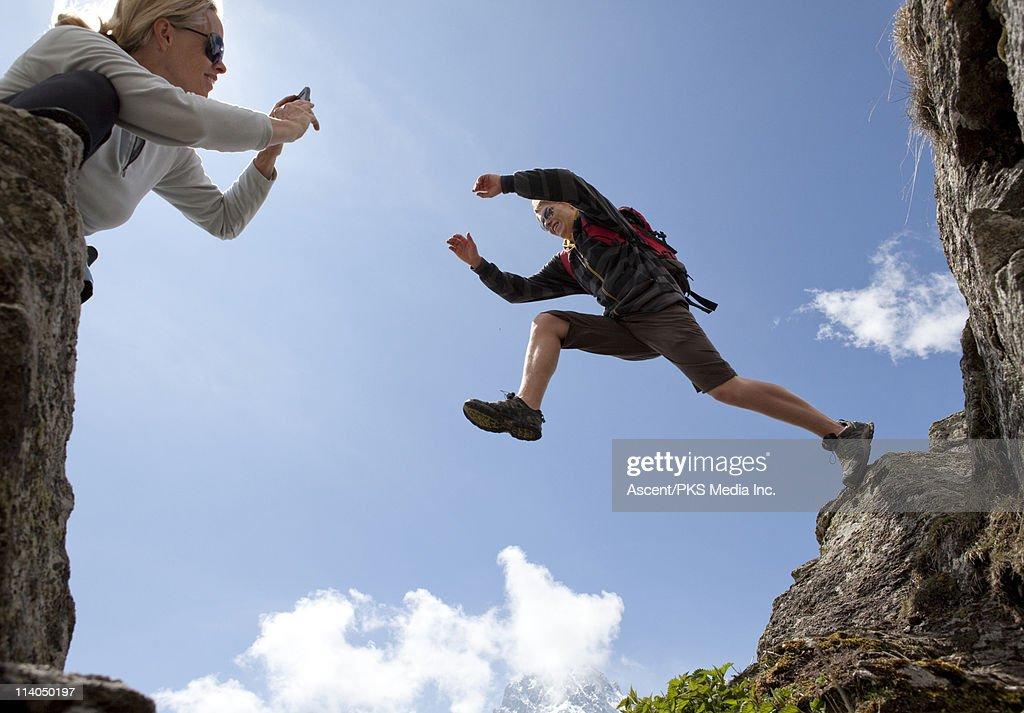 Teenage boy leaps across gap while mom takes pict : Stockfoto