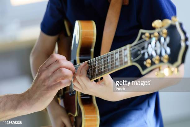 teenage boy learning electric guitar from trainer - guitarist stock pictures, royalty-free photos & images