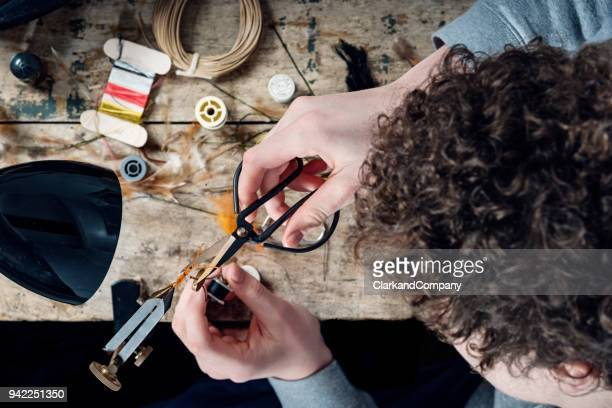 teenage boy learning how to make fishing flies - fishing hook stock pictures, royalty-free photos & images