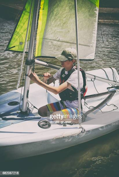 teenage boy learning to sail and tie knots on small sailboat - sail boom stock pictures, royalty-free photos & images