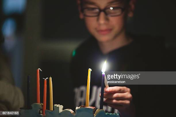 Teenage boy lighting Menorah during Hanukkah