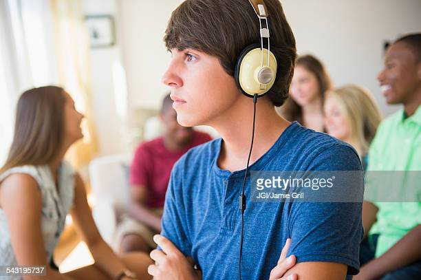 Teenage boy listening to headphones at party