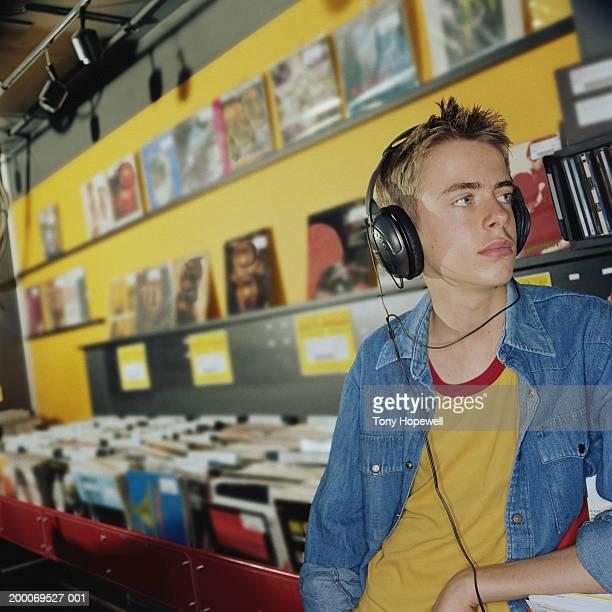 Teenage boy (14-16) listening to headphones in record shop