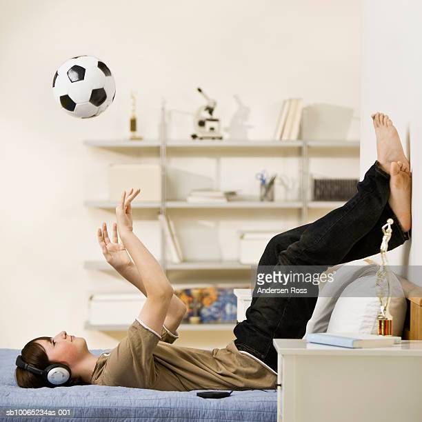 Teenage boy (13-14) listening to MP3 player, playing with soccer ball on bed
