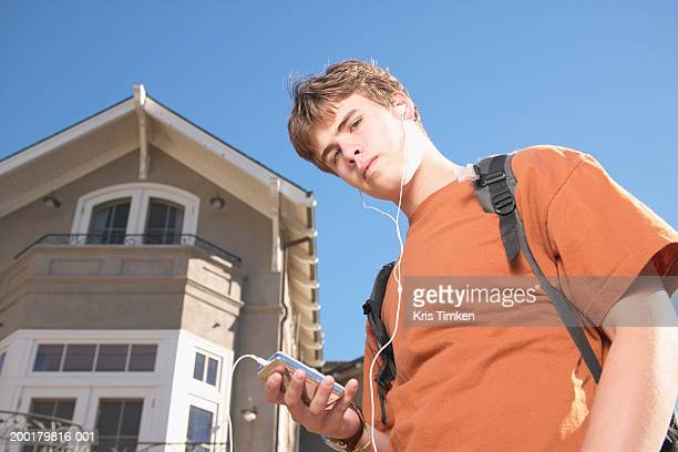 Teenage boy (14-16) listening to MP3 player, portrait, low angle view