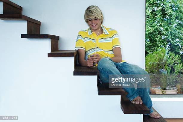 Teenage boy listening to music, sitting on stairs