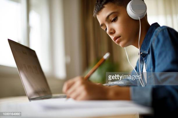 teenage boy listening to music while doing homework - online class stock pictures, royalty-free photos & images