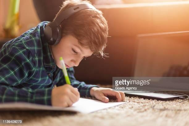 teenage boy luisteren naar muziek terwijl het doen van huiswerk - 10 11 jaar stockfoto's en -beelden