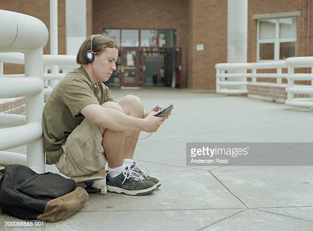 teenage boy (16-18) listening to walkman, sitting outside high school - personal compact disc player stock pictures, royalty-free photos & images