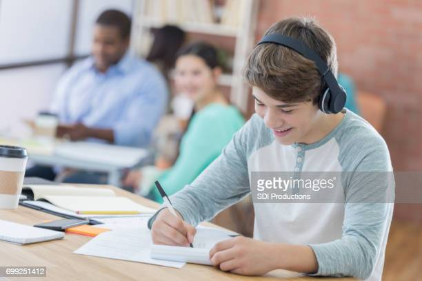 Teenage boy listens to music while studying