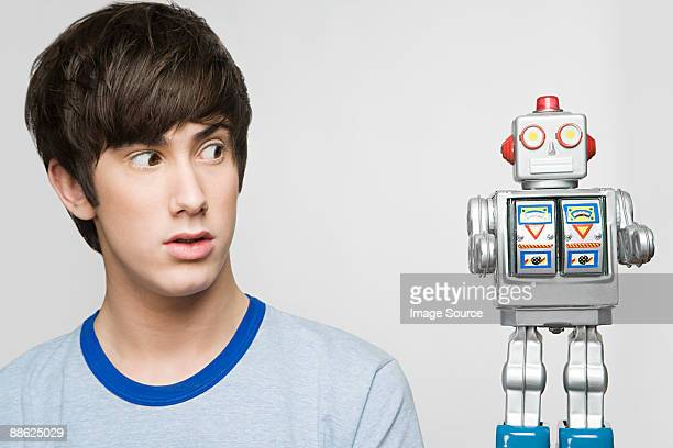 Teenage boy looking at a robot