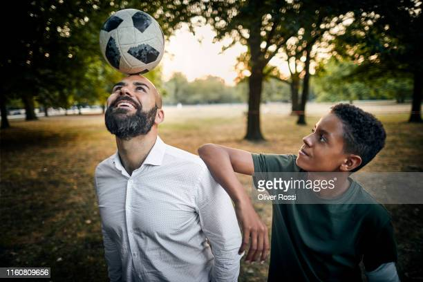 teenage boy looking at father balancing a soccer ball on his head in a park - football player photos et images de collection