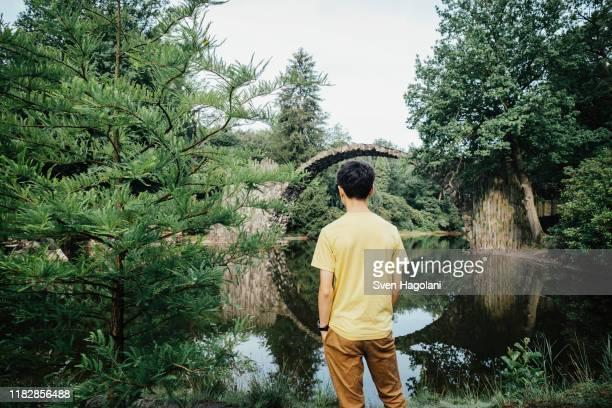 teenage boy looking at tranquil rakotzbruecke devils bridge, rakotzbruecke, brandenburg, germany - one teenage boy only stock pictures, royalty-free photos & images