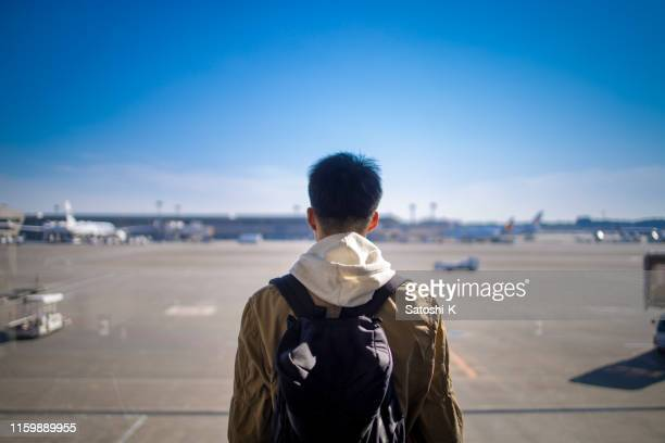 teenage boy looking at view from airport - narita stock pictures, royalty-free photos & images
