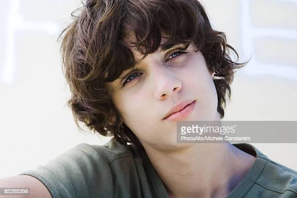 Teenage boy looking away, head tilted, portrait