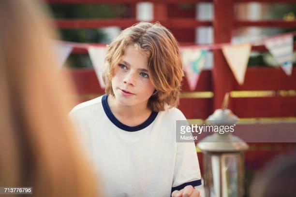 Teenage boy looking away in back yard
