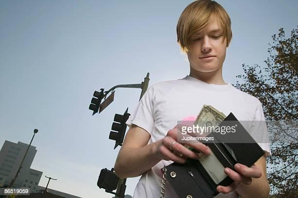 Teenage boy looking in wallet