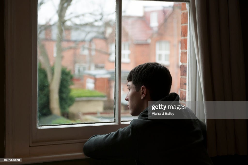 Teenage boy looking out of bedroom window : Stock Photo