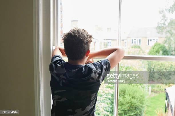 teenage boy looking out of bedroom window - verveling stockfoto's en -beelden