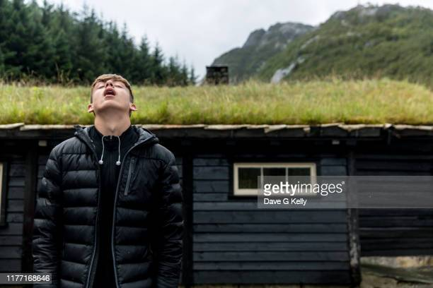 teenage boy looking skywards standing in front of grass roofed black cottage - padded jacket stock pictures, royalty-free photos & images