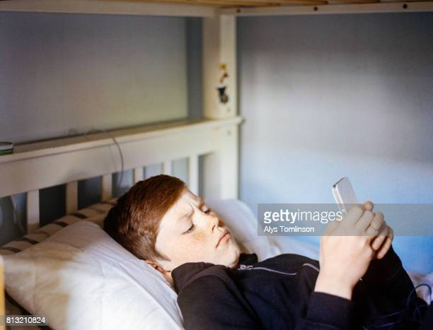 teenage boy lying in bed looking at his mobile phone - child facebook stock photos and pictures