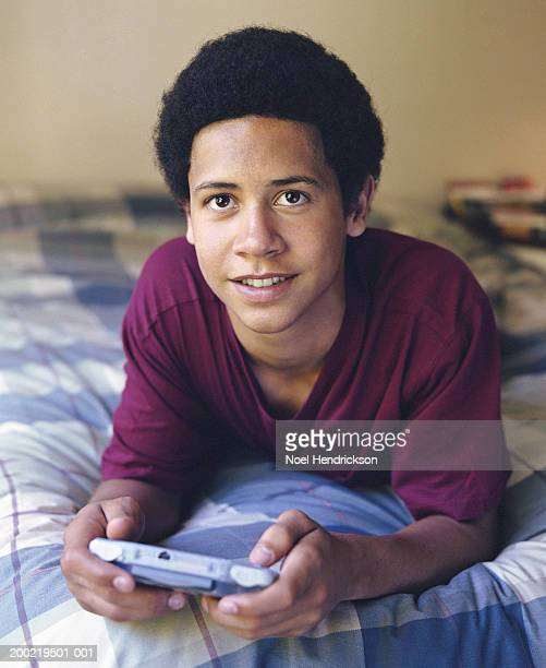 teenage boy (16-18) lying in bed, with hand held video game, portrait - one teenage boy only stock pictures, royalty-free photos & images