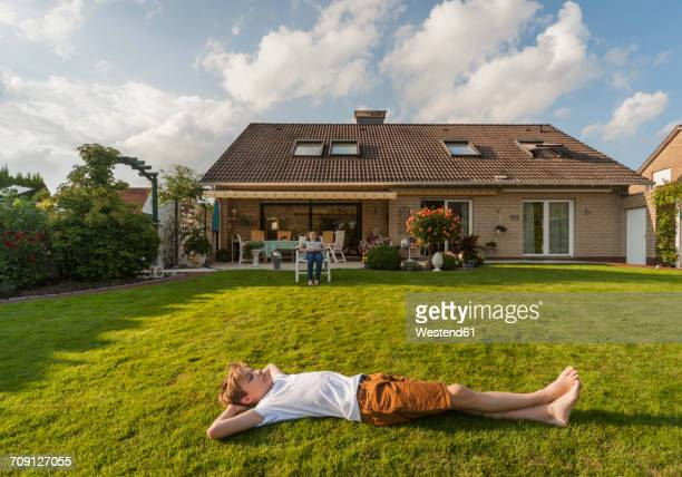 teenage boy lying in garden - teen boy barefoot stock photos and pictures