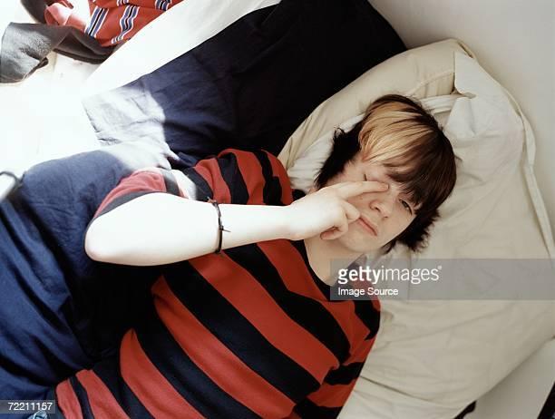 Teenage boy lying on bed
