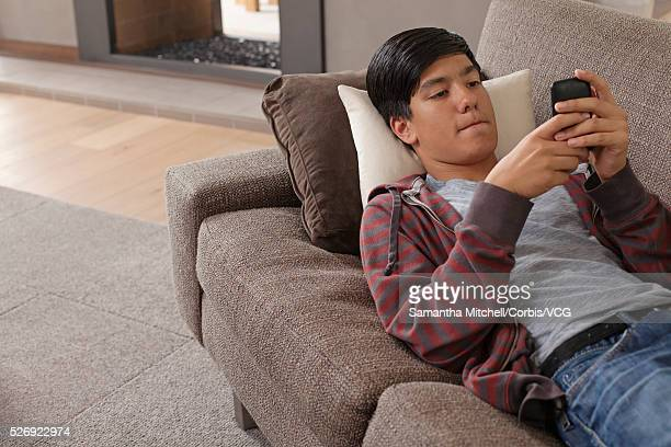 Teenage boy (16-17) lying on sofa using phone