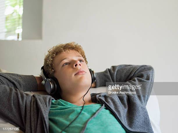 Teenage boy lying on the bed and listening to music