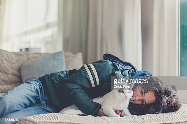 A teenage boy lying on the couch hugging his cat